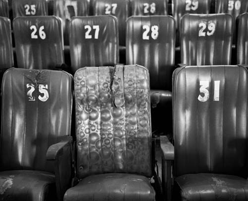photograph of old numbered theater chairs by Nandita Raman