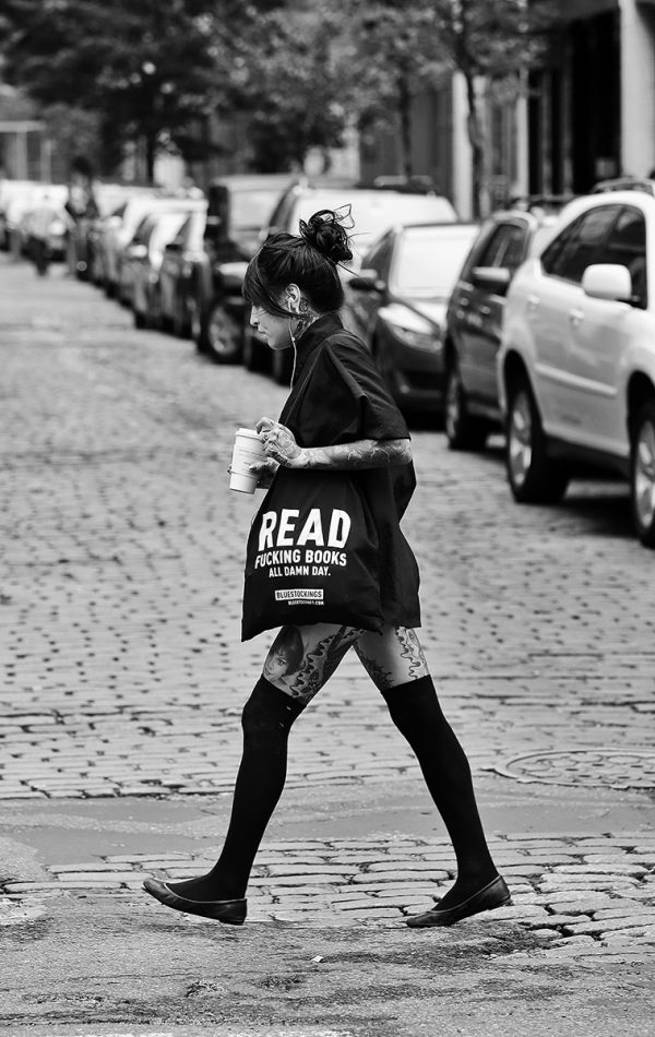 Woman with book bag that reads: READING FUCKING BOOKS ALL DAMN DAY crosses Prince & Wooster in Soho, NYC. July 18, 2015 by Lawrence Schwartzwald