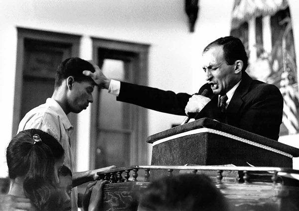 Preacher Baptising by Deyva Arthur